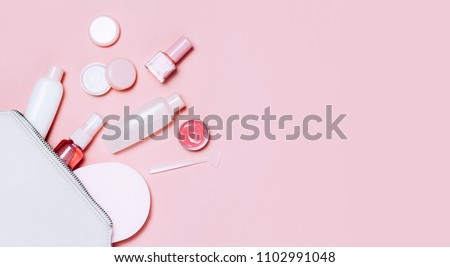 Beautiful Decorative cosmetic and creams set from cosmetic bag on pink background. Copyspace for your text. Minimalism cosmetics style. Top view, flat lay.
