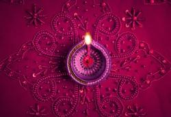 Beautiful decorative Diwali lamp on embellished purple background. Happy Diwali Greeting Card.