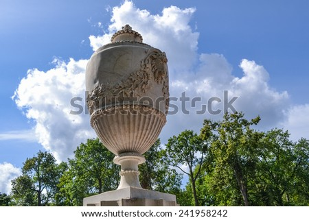 Beautiful decorative vase in the Park of Peterhof. White vase with floral ornaments on the background of trees and clouds. Antique vase, decoration of the Park.