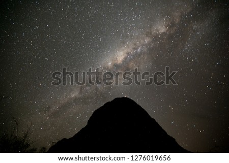 Beautiful defocused picture of milky way scenery with large silhouette termite nest on foreground at Karijini National Park Western Perth, Australia