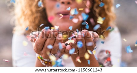 beautiful defocused woman blow confetti from hands. celebration and event concept. happiness and coloured image. movement and happiness having fun #1150601243