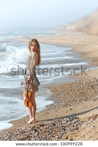 Beautiful delicate girl with violin on the seashore