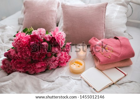 Beautiful delicate pink cashmere sweater is lying on linen bedclothes with peonies bouquet and candles. Womans fashion accessories, flowers, jewelry on grey background. Cozy morning. #1455012146