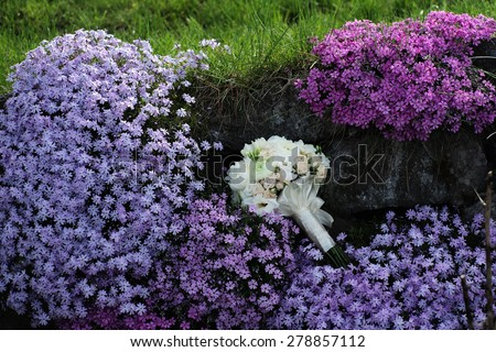 Beautiful delicate wedding bouquet of roses and peony in pastel colours lying among purple and violet flowering bushes  in broad daylight outdoor on natural background, horizontal picture