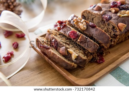 Beautiful delicious homemade Christmas dried fruit cake on wooden table with decorating items for celebrating festive season #732170842