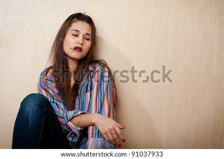 Beautiful depressed woman sitting by the wall with cigarette in mouth - stock photo