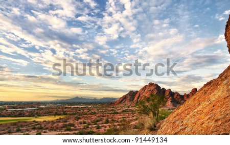 Beautiful desert landscape with red rock buttes and gorgeous summer glowing sky wit little fluffy clouds