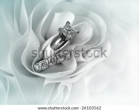 Beautiful diamond wedding ring set displayed in the folds of the fabric of a wedding gown. Space for copy.