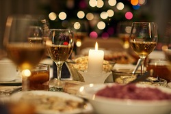 Beautiful dining table full of a variety of delicious festive food and wine with a Christmas tree in the background in candle ight mood