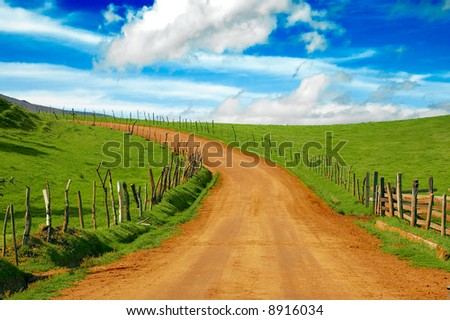 beautiful dirt road and meadow - stock photo