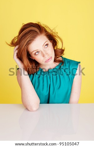 Beautiful distracted woman with dishevelled hair seated at a table looking up at the ceiling