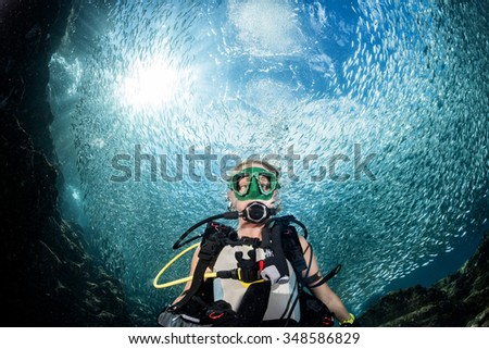 beautiful diver blonde girl diving in the deep blue sea  Inside a school of fish