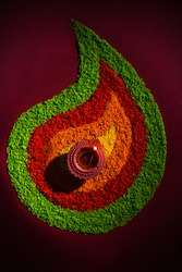 Beautiful Diwali Greeting using Diya or clay oil lamp lit and arranged over Rangoli made by multi coloured rice grains, selective focus