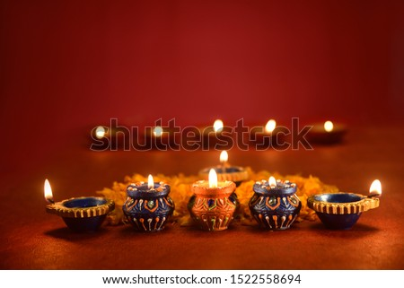 Beautiful diwali lamps with flowers on red background, Diwali Diya