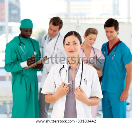 Beautiful doctor with her team in the background in hospital
