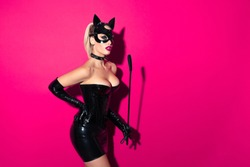 Beautiful dominant blonde vamp mistress bdsm girl with fashion makeup in glamour latex skirt, corset, collar and bdsm black leather fetish cat mask posing with whip on hot pink background