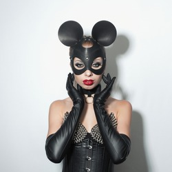 Beautiful dominant blonde vamp mistress girl in leather corset, gloves, collar and bdsm black leather fetish cat mask posing on white backgroung