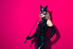 Beautiful dominant blonde vamp mistress girl with fashion makeup in glamour latex dress, collar, corset and bdsm black leather fetish cat mask posing on hot pink backgroung