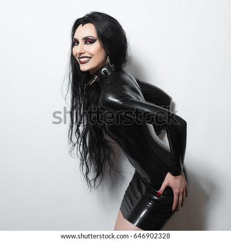Beautiful dominant brunette vamp fetish goth mistress evil girl in black latex dress and bdsm spiky leather collar posing on white backgroung