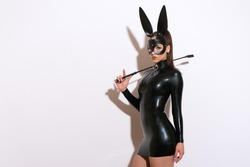 Beautiful dominant brunette vamp mistress bdsm girl with fashion makeup in glamour latex dress, collar and bdsm black leather fetish rabbit mask posing on white background