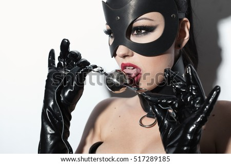 Beautiful dominant brunette vamp mistress girl in latex corset, long gloves, collar and bdsm black leather fetish mouse mask posing with metal ball gag on white backgroung