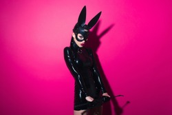 Beautiful dominant brunette vamp mistress girl with fashion makeup in glamour latex dress, collar and bdsm black leather fetish rabbit mask posing on hot pink backgroung
