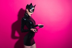 Beautiful dominant brunette vamp mistress girl with fashion makeup in glamour latex dress, collar and bdsm black leather fetish cat mask posing on hot pink backgroung