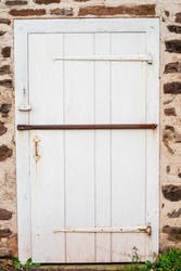 Beautiful door with long antique hinges sits shut in a stone house, barred with a rusty antique bar. Natural light with copy space.
