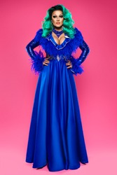 beautiful drag queen on a pink background in a blue dress and blue hair