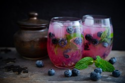 Beautiful, dramatic blueberry mojito image in dark moody style