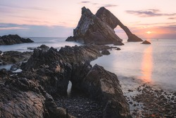 Beautiful dramatic sescape scenery at sunrise or sunset of Bow Fiddle Rock sea arch on the rocky shore of Portknockie on the Moray Firth in Scotland.