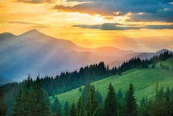 Beautiful dramatic sunset in the mountains. Landscape with sun light shining through orange clouds