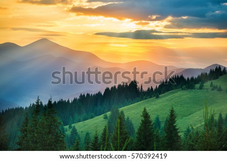 Beautiful dramatic sunset in the mountains. Landscape with sun light shining through orange clouds #570392419