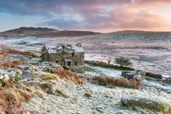 Beautiful dramatic sunset over an old abandoned granite stone cottage on the foothills of Brown Willy on Bodmin moor, the highest point in Cornwall