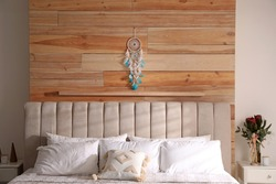 Beautiful dream catcher hanging above bed in stylish room interior