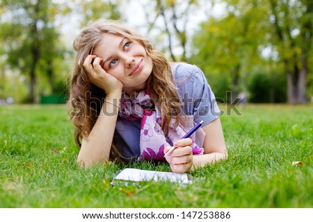 Beautiful dreamy teen girl lying on grass in park with pen and notebook