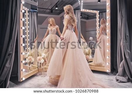 Beautiful dress.  Full length of attractive young woman wearing wedding dress while standing in front of the mirror in bridal shop