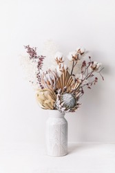 Beautiful dried flower arrangement in a stylish ceramic white vase. Dried flowers include pink proteas, banksia, gold palm leaf, kangaroo paw, cotton and ruscus leaves.