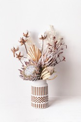 Beautiful dried flower arrangement in a stylish ceramic white vase with brown aztec pattern. Dried flowers include pink proteas, banksia, gold palm leaf, kangaroo paw, cotton and ruscus leaves.