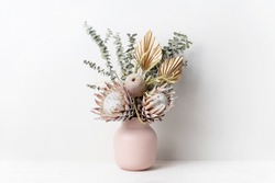 Beautiful dried flower arrangement in a stylish pink vase. In the flower bunch is pink King Proteas, Banksia, Eucalyptus leaves and golden Palm fronds, photographed on a white background.