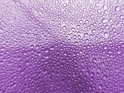 Beautiful drops of purple water on the glass. Good background for different purposes.