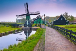 Beautiful dutch countryside street with traditional small wooden windmill, Zaanse Schans touristic village, Netherlands, Europe