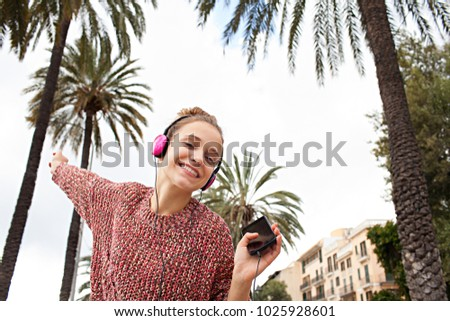 Beautiful dynamic young woman using smartphone and headphones to listen to music, dancing singing in city avenue, recreation leisure. Female teenager with technology, free living lifestyle, outdoors.