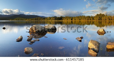Beautiful early morning light over a tranquil lake. Photographed at Loch Morlich, Cairngorms, Scotland. #611457185