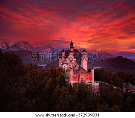 Beautiful early morning view of the Neuschwanstein fairy tale castle, bloody dark sky with autumn colours in the trees during sunrise, twilight, end of night, Bavarian Alps, Bavaria, Germany