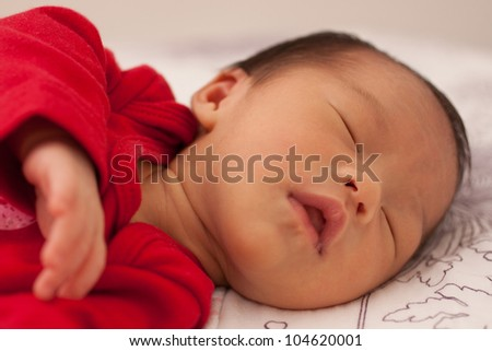 Beautiful East Asian Baby Infant Girl Sleeping Soundly in Red Outfit