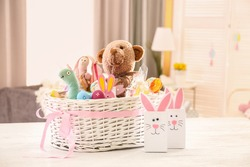 Beautiful Easter basket with traditional decorations and sweets near cute gift bags on white table