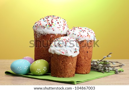 Beautiful Easter cakes, colorful eggs and pussy-willow twigs on wooden table on yellow background
