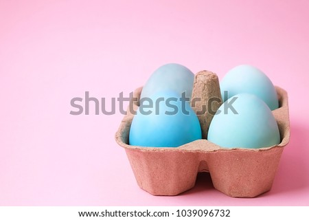 Beautiful easter table setting festive composition. Four solid blue color eggs in carton on pink table top background. Minimalistic holiday scene. Top view, copy text space.