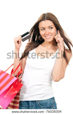 Beautiful ecstatic woman holding shopping bags and credit gift-card in hand, talking by cell phone mobile on a white background